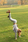 Girl training handstand. Exercising little kid - girl in grey clothes and brown shoes training handstand on green grass of football stadion Royalty Free Stock Images