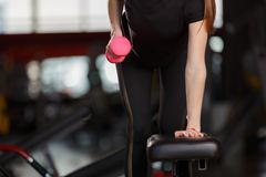A girl is training her back muscles. With the help of a bright pink dumpbell in a sportsgym royalty free stock photos