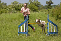 Girl training her dog to jump Royalty Free Stock Photography
