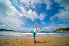 The girl training on the beach. The girl training with the long wooden stick on the beach in summer stock image