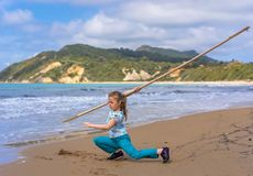 The girl training on the beach. The girl training with the long wooden stick on the beach in summer royalty free stock image