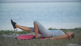 Girl is training near the sea. In the evening stock footage