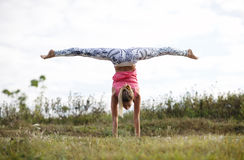 Girl training outdoor. Young girl training outdoors: suppling exercises standing on hands Royalty Free Stock Photo