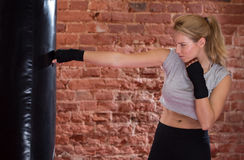 Girl training with punch bag Stock Image