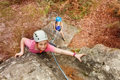 Girl training rock climbing in forest area. Top view portrait of of teenage girl in helmet training rock climbing with female instructor in forest area stock photo