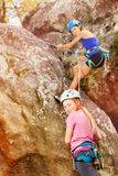 Girl training rock climbing with instructor Royalty Free Stock Photo