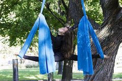 Girl training on silks on open air. Young gymnast doing exercise on aerial silks Royalty Free Stock Images