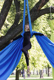 Girl training on silks on open air. Young gymnast doing exercise on aerial silks Royalty Free Stock Image