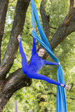 Girl training on silks on open air. Young gymnast doing exercise on aerial silks Stock Photo