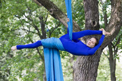 Girl training on silks on open air. Young gymnast doing exercise on aerial silks Stock Images