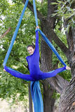 Girl training on silks on open air. Young gymnast doing exercise on aerial silks Stock Photos