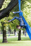 Girl training on silks on open air. Young gymnast doing exercise on aerial silks Royalty Free Stock Photos
