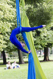 Girl training on silks on open air. Young gymnast doing exercise on aerial silks Stock Photography