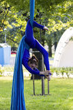 Girl training on silks on open air. Young gymnast doing exercise on aerial silks Royalty Free Stock Photography
