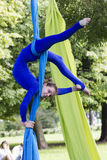 Girl training on silks on open air. Young gymnast doing exercise on aerial silks Royalty Free Stock Photo