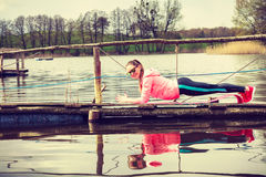 Girl training in sporty clothes on lake shore Royalty Free Stock Photography
