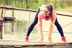 Girl training in sporty clothes on lake shore Royalty Free Stock Photos