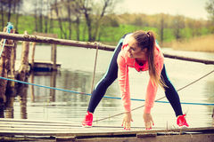 Girl training in sporty clothes on lake shore Royalty Free Stock Image