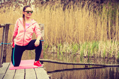 Girl training in sporty clothes on lake shore Stock Photography