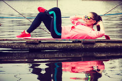 Girl training in sporty clothes on lake shore Royalty Free Stock Photo