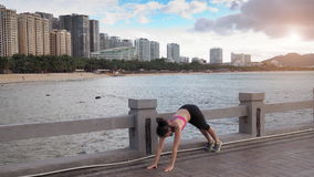 Girl is training yoga on the beach. Near sea and city stock footage
