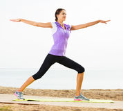 Girl training yoga poses. Smiling young girl training yoga poses standing on beach on sunny morning Royalty Free Stock Photos