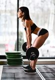 Girl trains with a barbell royalty free stock image