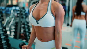 A girl trains the muscles of the arms with dumbbells. In the frame are only visible hands and upper body to the head. The woman at the same time bending and stock footage
