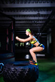 The girl trains the muscles of her legs in the gym jumping on a large tire. Sports lifestyle concept royalty free stock photos