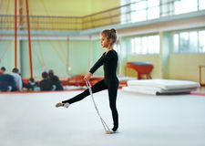 Girl trains with  rope in rhythmic gymnastics. Stock Photo