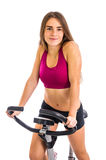 Girl trains on stationary bicycle Royalty Free Stock Photography