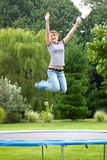 Girl on Trampoline. Girl jumping high on trampoline, motion Royalty Free Stock Photos