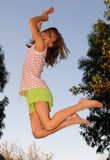 Girl on trampoline. Little girl jumping on trampoline against blue sky Royalty Free Stock Images