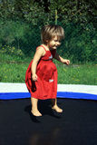 Girl on trampoline. Happy little girl in red dress jumping on trampoline outdoors Royalty Free Stock Image