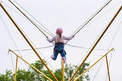 Girl on a trampoline with elastic bands stock photography