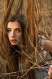 Girl trapped in the grass. Girl having problem with her long hair in high grass Stock Images