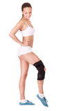 Girl with trauma of knee in brace. Royalty Free Stock Image