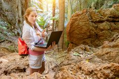 Girl travel agent. Develops a new tourist route for tourist excursions through the mountains and jungles. Works with cards in a. Laptop. Shows gesture `super` royalty free stock photo