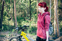 Girl travel bicycle backpack. Forest redhead sport Royalty Free Stock Images