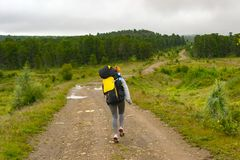 Girl travel with big black backpack and bottle of water in it go stock images