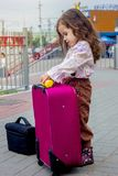Girl with the travel case on the railway station ready to travel. Stock Image