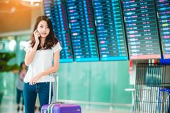 Girl in travel moment. Asian teenage girl is using a smartphone to check flight at the international airport to travel on weekends Royalty Free Stock Photo