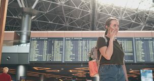 Girl traveler at the airport to talk on a mobile phone. Standing at the display with information about the departure of aircraft at the airport, a young girl stock video