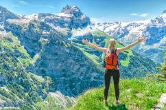 Girl traveler, arms outstretched, against the backdrop of mounta. In peaks, the Engelberg resort, Switzerland Stock Image