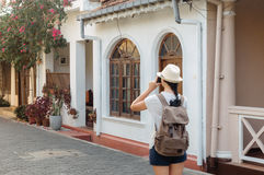 Girl traveler with a backpack and camera on the street Royalty Free Stock Photos
