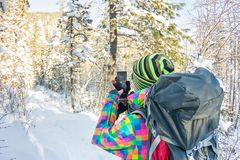 Girl traveler with backpack doing selfie on phone in winter forest Stock Photography