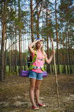 Girl traveler with backpack looks into distance. Travel and tourism concept. Teenage girl traveler with backpack climb in hill forest. Adventure, travel, tourism Stock Photos
