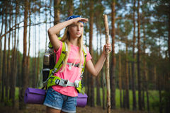 Girl traveler with backpack looks into distance. Travel and tourism concept. Teenage girl traveler with backpack climb in hill forest. Adventure, travel, tourism Royalty Free Stock Image