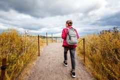 Girl traveler with a backpack walks around the island of Suomenlinna in a beautiful autumn day, a trip to nature in Northern Euro royalty free stock photo