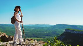 The girl traveler in a cowboy hat and white clothes stands on the top of the mountain and admires the stunning views of. A beautiful red-haired traveler girl in stock video
